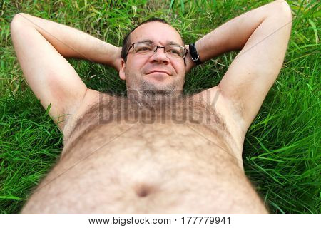 Lazy person. A man with a big belly lies on the grass.
