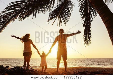 Happy family of mother father and young daughter stands under palm tree with rised hands. Beach holidays concept
