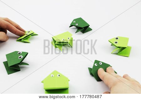Hands playing the jumping frog game made from origami