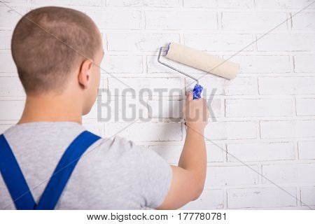 Back View Of Man Painter In Workwear Painting Brick Wall With Paint Roller