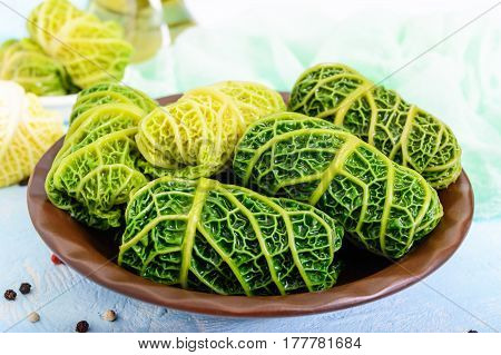 Leaves of Savoy cabbage stuffed with minced meat and rice in a clay bowl on a light background.