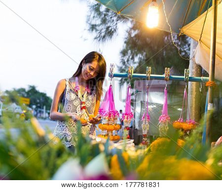 Woman buying flower at hawker in thailand