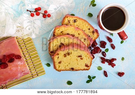Soft festive fruitcake with raisins and dried cranberries decorated with sugar icing cut by pieces and cup of coffee on a light background. Top view.