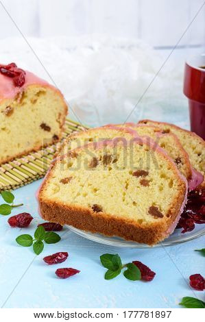 Soft festive fruitcake with raisins and dried cranberries decorated with sugar icing cut by pieces and cup of coffee on a light background. Vertical view