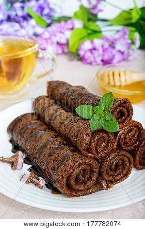 Thin delicate chocolate pancakes rolled laid out in a pile on a white plate and a cup of herbal tea with honey. Vertical view