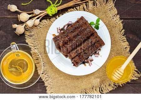 Thin delicate chocolate pancakes rolled laid out in a pile on a white plate and a cup of herbal tea with honey. The top view