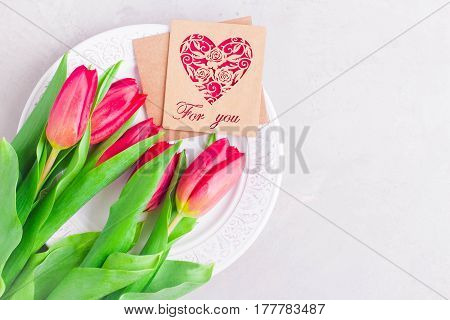 Easter Table Setting. White plate pink tulips and paper letter card on table background. Horizontal image phototop view and copy space