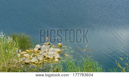 The fisherman in swimming trunks on the shore of the lake