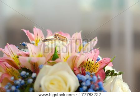 Gold wedding rings on a wedding bouquet of bright flowers