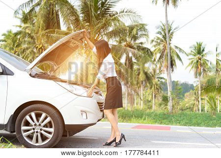 Business woman standing by broken car and looking to engine