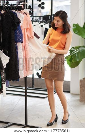 Smiling beautiful woman choosing dress in mall