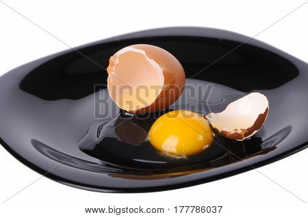The cracked egg on a black plate