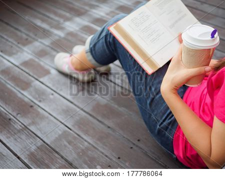 Young pretty woman sitting at outdoor drinking coffee and reading a book enjoys of rest