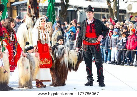 Razlog, Bulgaria - January 14, 2017: People, adults and children in traditional carnival kuker costumes clothing at Kukeri festival Starchevata