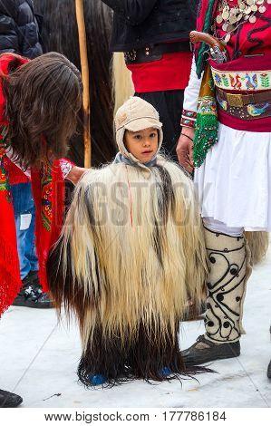 Razlog, Bulgaria - January 14, 2017: Child in traditional carnival kuker costumes at Kukeri festival Starchevata