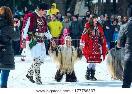 Razlog, Bulgaria - January 14, 2017: People, adults and children in traditional carnival kuker costumes at Kukeri festival Starchevata