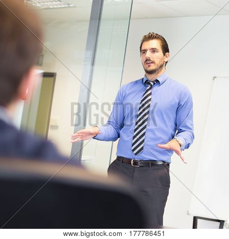 Business man making a presentation at office. Business executive delivering a presentation to his colleague during meeting or in-house business training, explaining business plans to his employee.