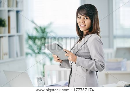 Portrait of smling attractive business lady with tablet computer