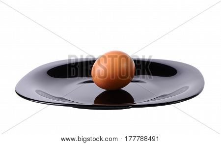 Egg on a black plate isolated on white