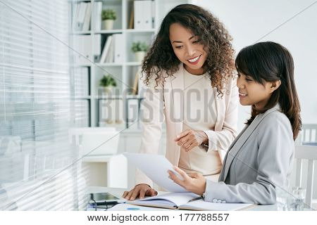 Female business colleagues discussing information in document
