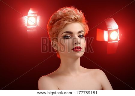 Delicate beauty. Young beautiful blonde woman posing confidently in red artistic lighting in studio wearing red lipstick and dark eye shadows makeup visage maquillage cosmetics beauty products concept
