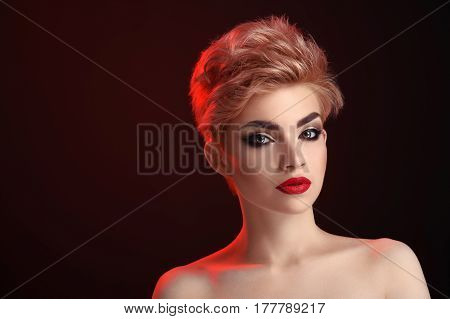 Perfect look. Attractive young female fashion model posing in red artistic lighting at studio on black background black smoky eyes red lips cosmetics beauty professional makeup concept copyspace
