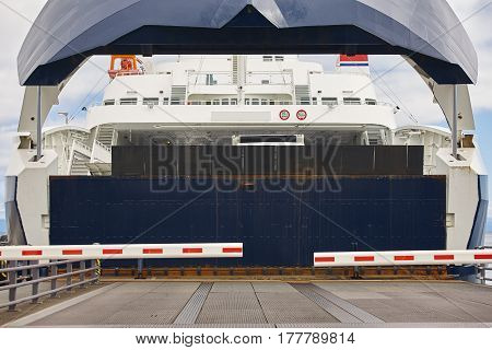Norwegian car ferry landing at port. Closed barrier. Horizontal