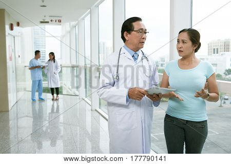 Doctor with tablet computer consulting female mature patient