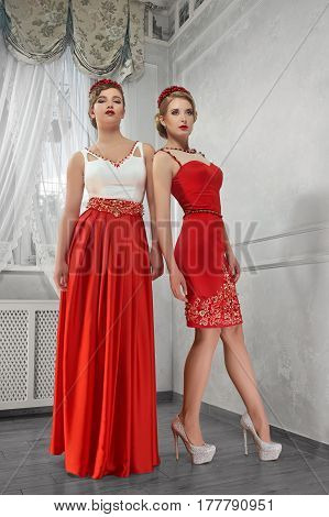 Two young, beautiful women in long red dresses standing shoulder to shoulder on hills on white background in the room.