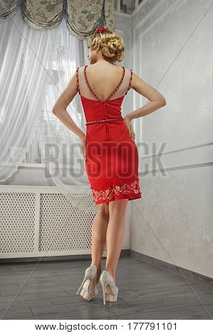 Young beauty woman, magnificent woman in red dress, on hills, hands on hips, back view.