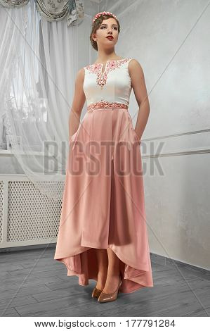 Young beauty, pretty woman in peach long dress, hand on hip, looking ahead.