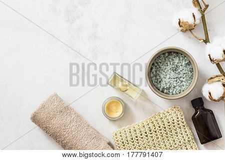 Spa beauty cosmetic products and tools on white marble background. Top view copy space