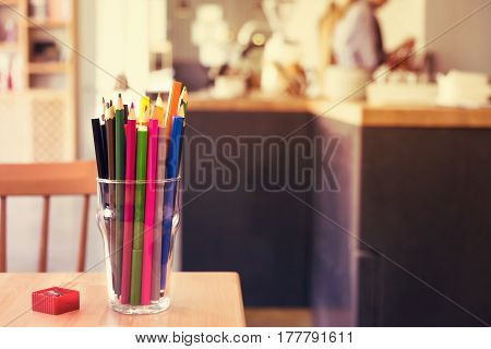 Colorful pencils in glass toned. Cafe interior. Creative ideas concept