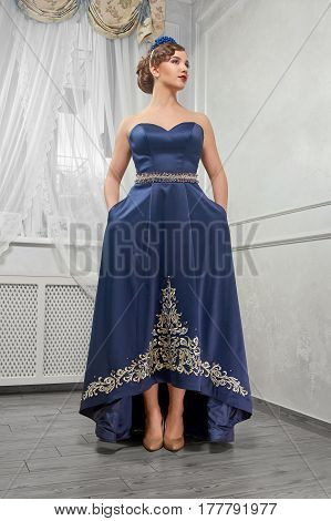 Elegant, beautiful, fashionable woman, girl, brunette in a long blue dress with embroidery, hands in the pockets of clothes in the room beige shoes.