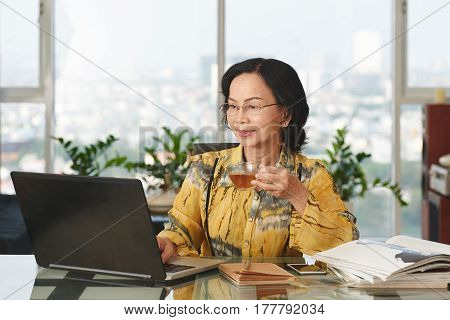 Asian mature business lady drinking tea and reading information on laptop screen
