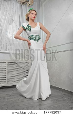 Elegant, beautiful, fashionable woman blonde in a long white dress with green embroidery, hands on hips, in room, full-length portrait.
