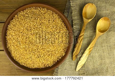 Dry bulgur wheat in a clay bowl with spoon on the table and sacking