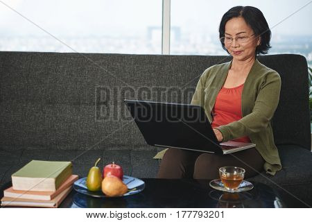 Aged business woman sitting on sofa and working on computer
