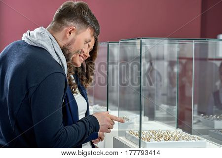 Variety hard to choose from. Shot of a young couple in love looking at the rings on a jewelry store display