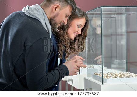 Day of a special choice. Beautiful young woman smiling choosing a ring with her beloved man pointing at the jewelry store display