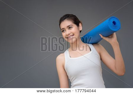 Young Asian Woman With Happy Smile Holding Her Yoga Mat At Yoga Healthy Sport Gym. Yoga And Meditati