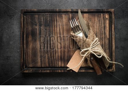 Table setting fork knife and wooden plate. Dark food background. Top view copy space.