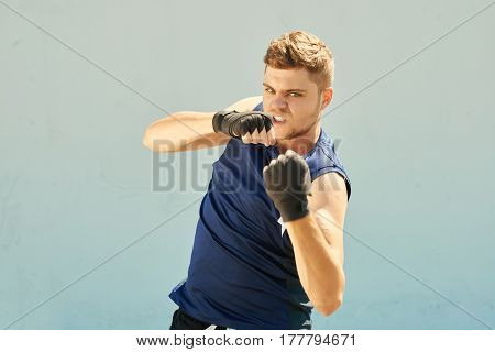 Young aggresive man boxing , isolated on grey