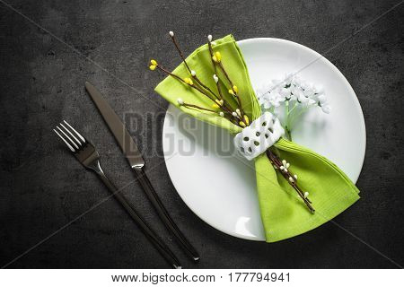 Table setting. Fork knife and white plate at dark slate table with spring decorations. Top view copy space.