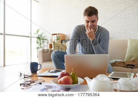 Smiling young man reading something on laptop screen