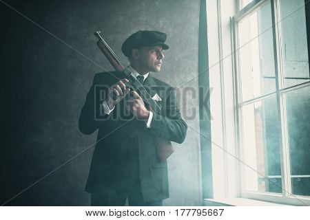 Retro 1920S English Gangster Wearing Flat Cap And Suit. Standing With Gun Looking Out Window.