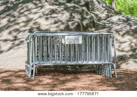 Metal fence barrier for crowd control or security event keep together in the national park behind the rocks.