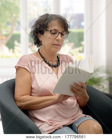 portrait of brunette mature woman with glasses reading a book