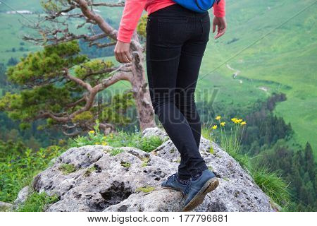 Young Woman Traveler With Backpack Hiking In Mountains With Beautiful Summer Landscape On Background