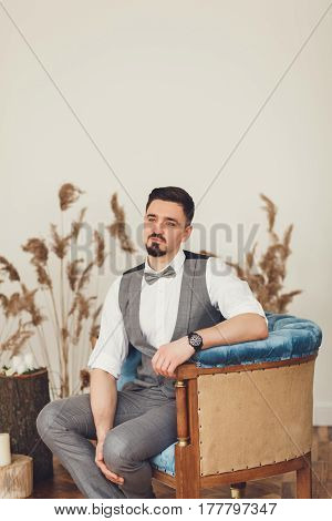 Groom with bow tie sits in a chair